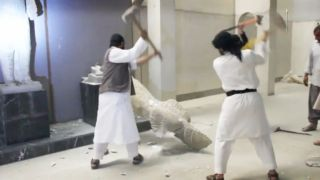 ISIS militants destroy two statues of kings from the ancient city of Hatra.