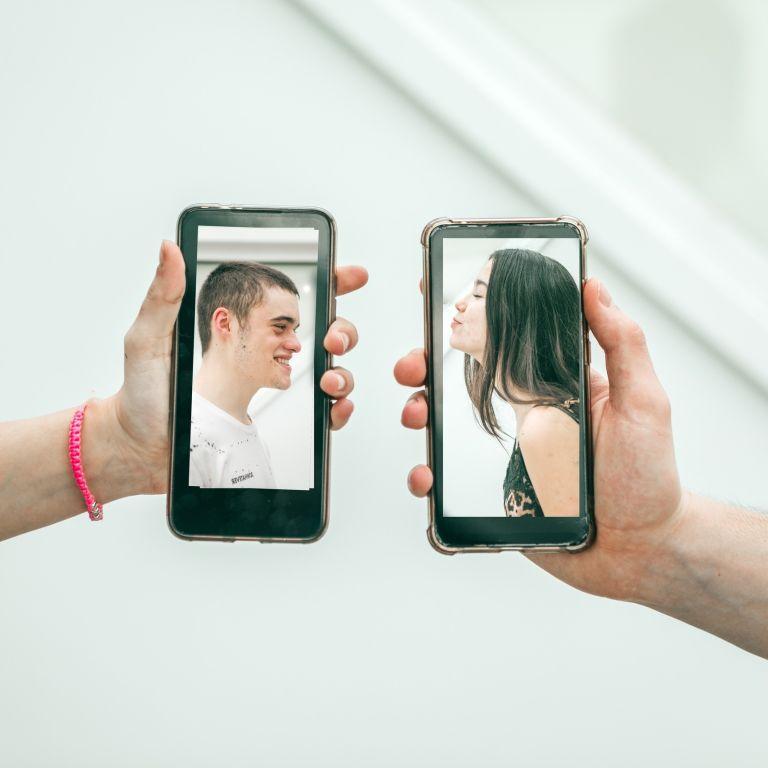 millennial couple kissing via mobile devices