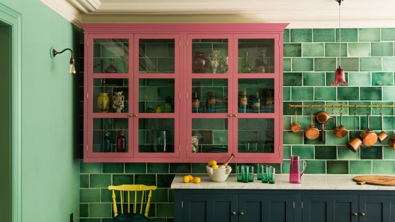 Green tiled kitchen with prink wall cabinet