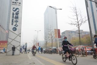 A cyclist rides through smog in Shenyang.