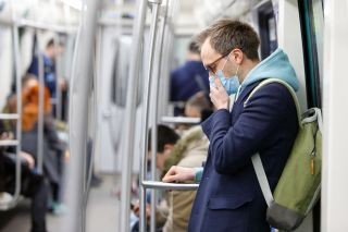 masked man coughing on the subway