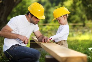A little boy helps his dad measure lumber.