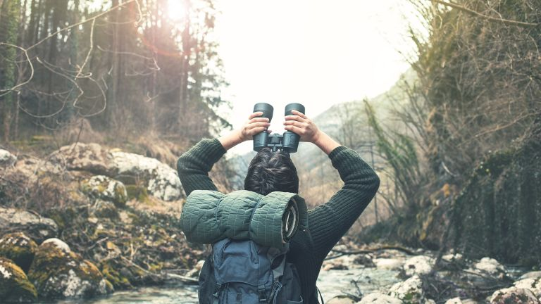Best binoculars: a man birdwatching while hiking