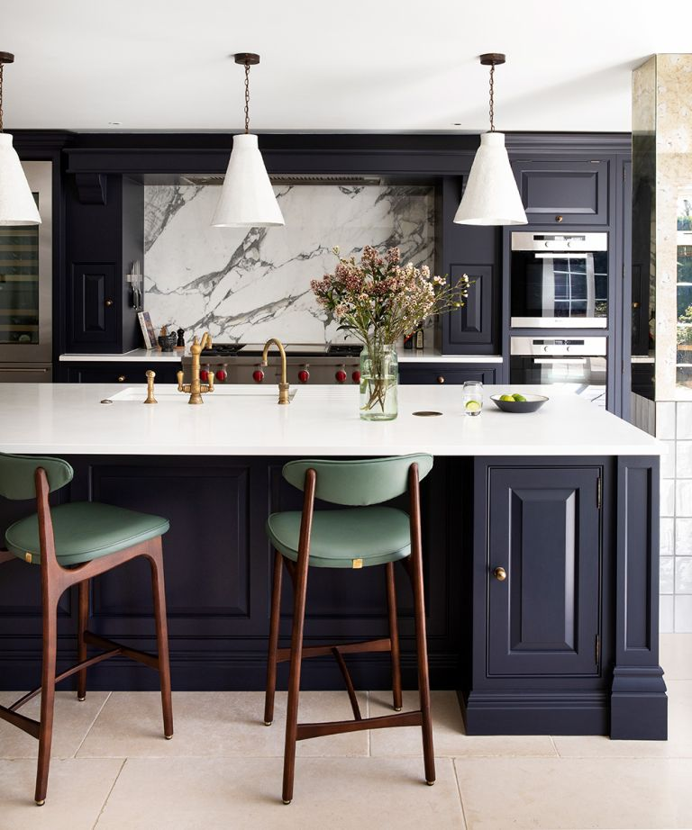 An example of how to choose kitchen lighting with pendant lights over a marble counter with dark blue cabinetry.