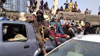 Taliban fighters sit on a vehicle along the street in Jalalabad province on Aug. 15, 2021.
