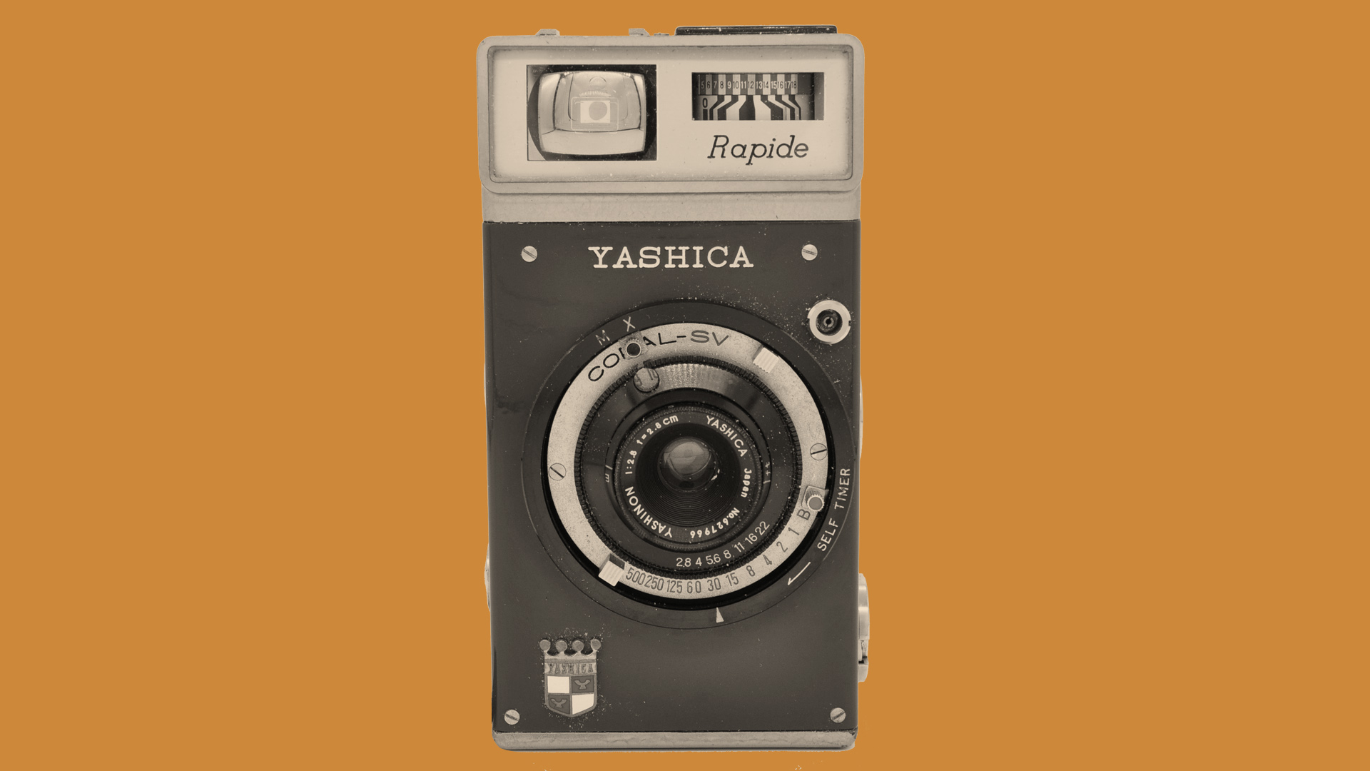 The front of the Yashica Rapide camera on a orange background