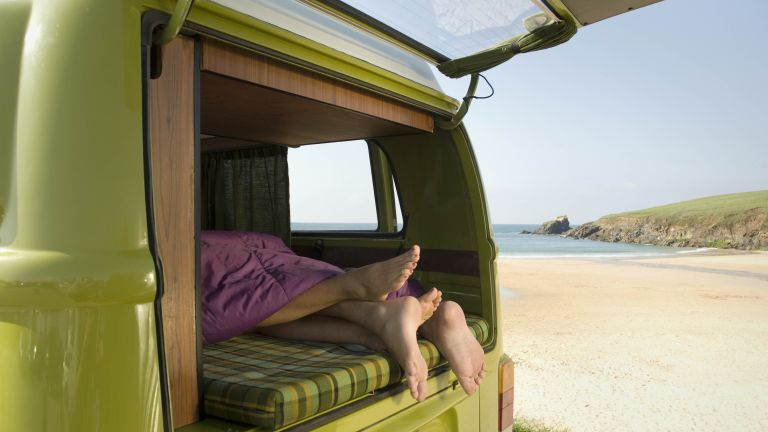 couple's feet in camper van on beach