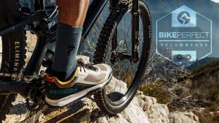Looking down a mountain as a MTB rider rolls over some rocks wearing Specialized Rime shoes