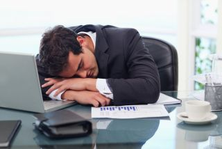 A man sleeps at his desk in an office.