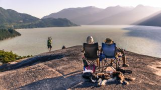 best camping chair: campers sitting on chairs by a lake