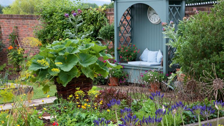 Vegetable garden container ideas in a garden with arbor and brick wall