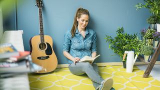 Girl reads a book sat next to her acoustic guitar