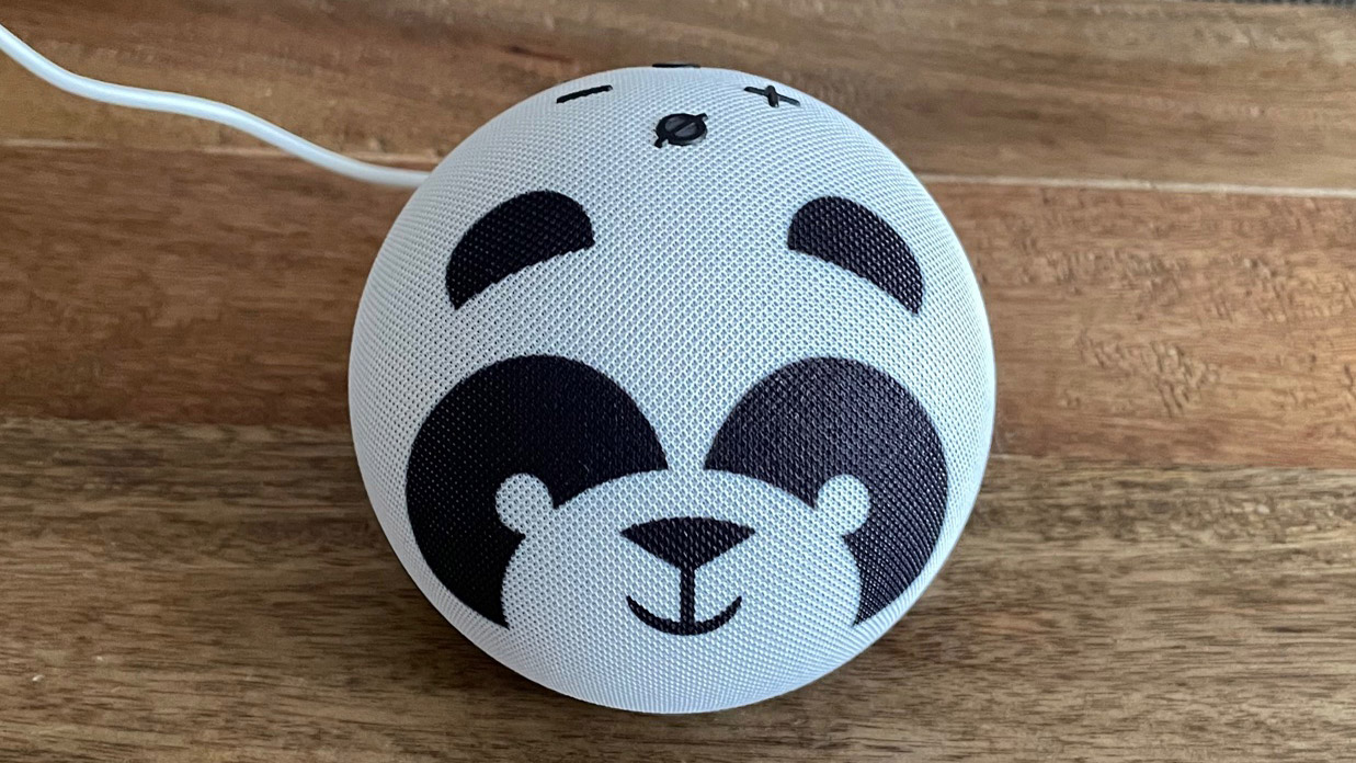 The top view of a Amazon Echo Dot Kids smart speaker on a wooden table with a patterned background