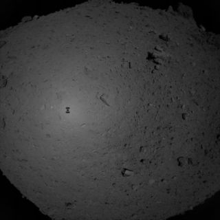 An image of the Hayabusa2 spacecraft silhouetted against Ryugu's surface, captured by the probe during its sampling procedure in February.