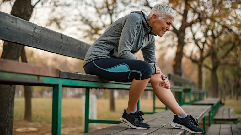 Older lady sits on a bench as she holds her leg in pain