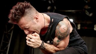 Greg Puciato screaming into a microphone