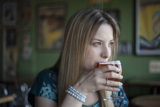 A blue-eyed woman sits, drinking a beer.
