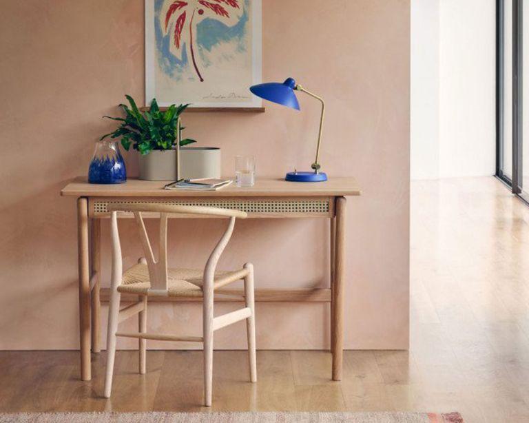 brass and cobalt blue desk light with wooden desk and plaster effect walls