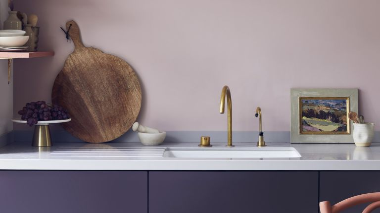 Lavender painted kitchen with golden tap and chopping board
