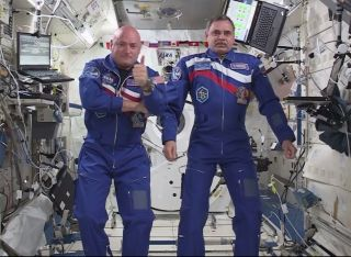 NASA astronaut Scott Kelly (left) gives a thumb's up sign while floating next to fellow one-year crewmate Mikhail Kornienko of Russia on the International Space Station after a video chat with NASA chief Charles Bolden and others on March 30, 2015. The sp