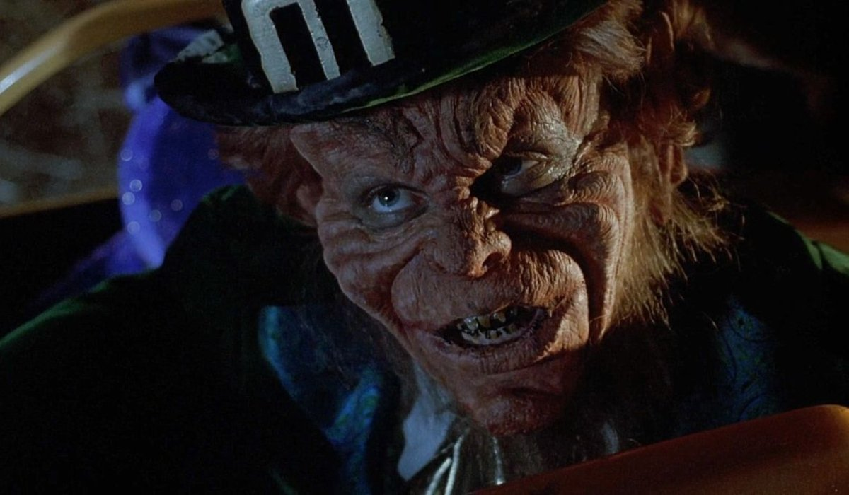 Warwick Davis grinning in full makeup in Leprechaun.
