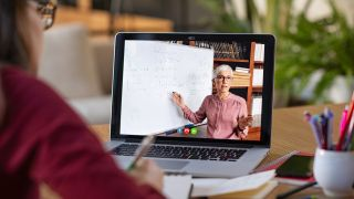 Woman sat in front of laptop, which shows woman pointing at whiteboard