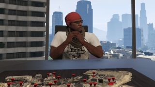 A GTA 5 Online player sits at a map in their office, fingers steepled.