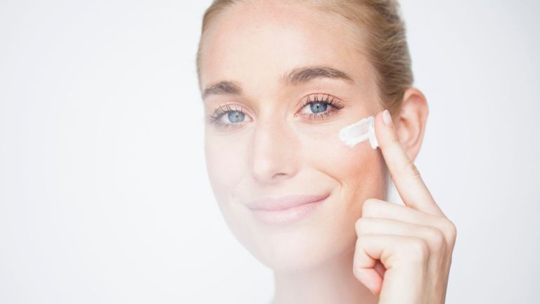 how to use retinol main image of woman with crows feet applying cream on her face