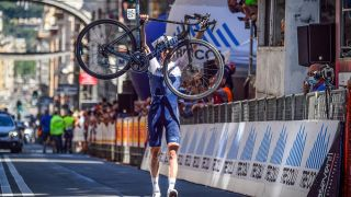 Israel Startup Nation rider holding his Factor bike in the air across the finish line