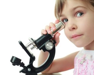 A young girl looks through a microscope.