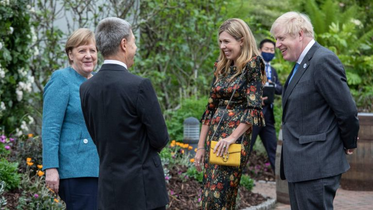 Germany's Chancellor Angela Merkel (L) and her husband, Joachim Sauer (2nd L) speak to Britain's Prime Minister Boris Johnson (R) and his wife Carrie Johnson at a reception with G7 leaders at The Eden Project in south west England on June