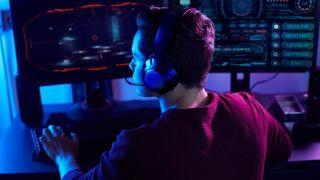 En PC-spelare som använder JBL Quantum 350 i ett mörkt rum