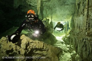 Divers roll out a guide string as they swim through the Sac Actun cave system.