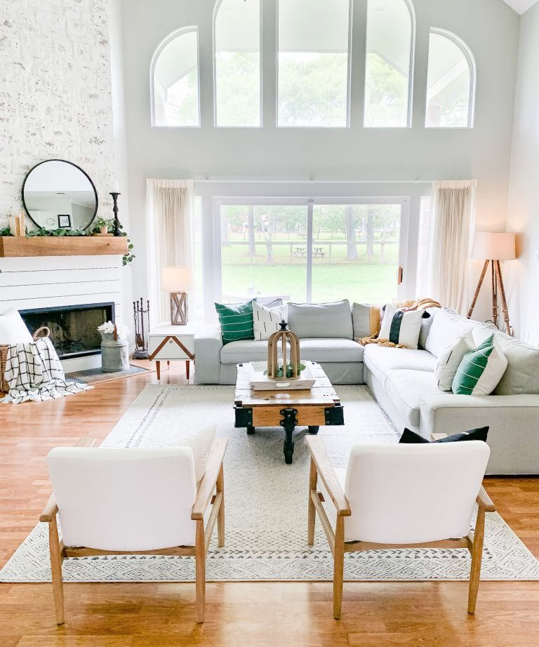 Corner fireplace in white living room with fabric and wooden armchairs, big area rug and coffee table