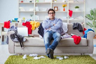Man sitting on couch in a messy room.