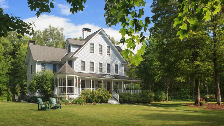 Victorian home with lawn and large front porch in summer