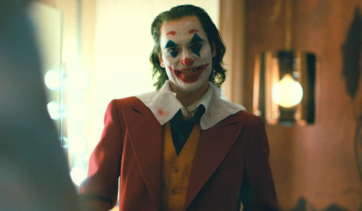 Joker smiling in the green room, after his makeup is finished