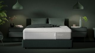 Best Casper mattress deals and discounts: An image of the Wave Hybrid Mattress set in a stylish, dark green colored bedroom