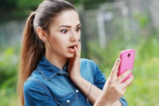 A woman looking surprised at her smartphone.