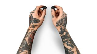 Tattooed hands holding a pair of Marshall Motif ANC earbuds