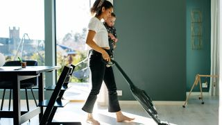 Survey reveals 91% prefer vacuums without hold triggers, but Dyson disagrees: image of woman operating cordless vacuum