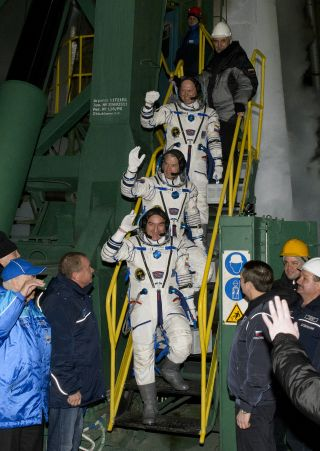 Expedition 39 Soyuz Commander Alexander Skvortsov of the Russian Federal Space Agency, Roscosmos, bottom, Flight Engineer Steve Swanson of NASA, middle, and Flight Engineer Oleg Artemyev of Roscosmos, wave farewell prior to boarding the Soyuz TMA-12M rock