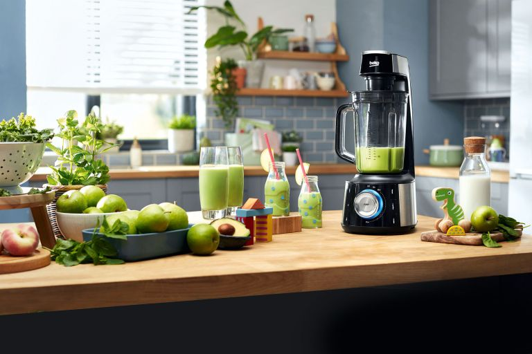 blender on countertop with apples and drinks