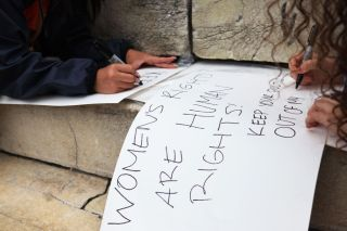 Women write protest signs at a reproductive rights rally