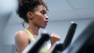 How to increase lung capacity: Close-up of a woman running on a treadmill