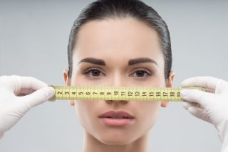 A woman's face is measured by a tape measure.