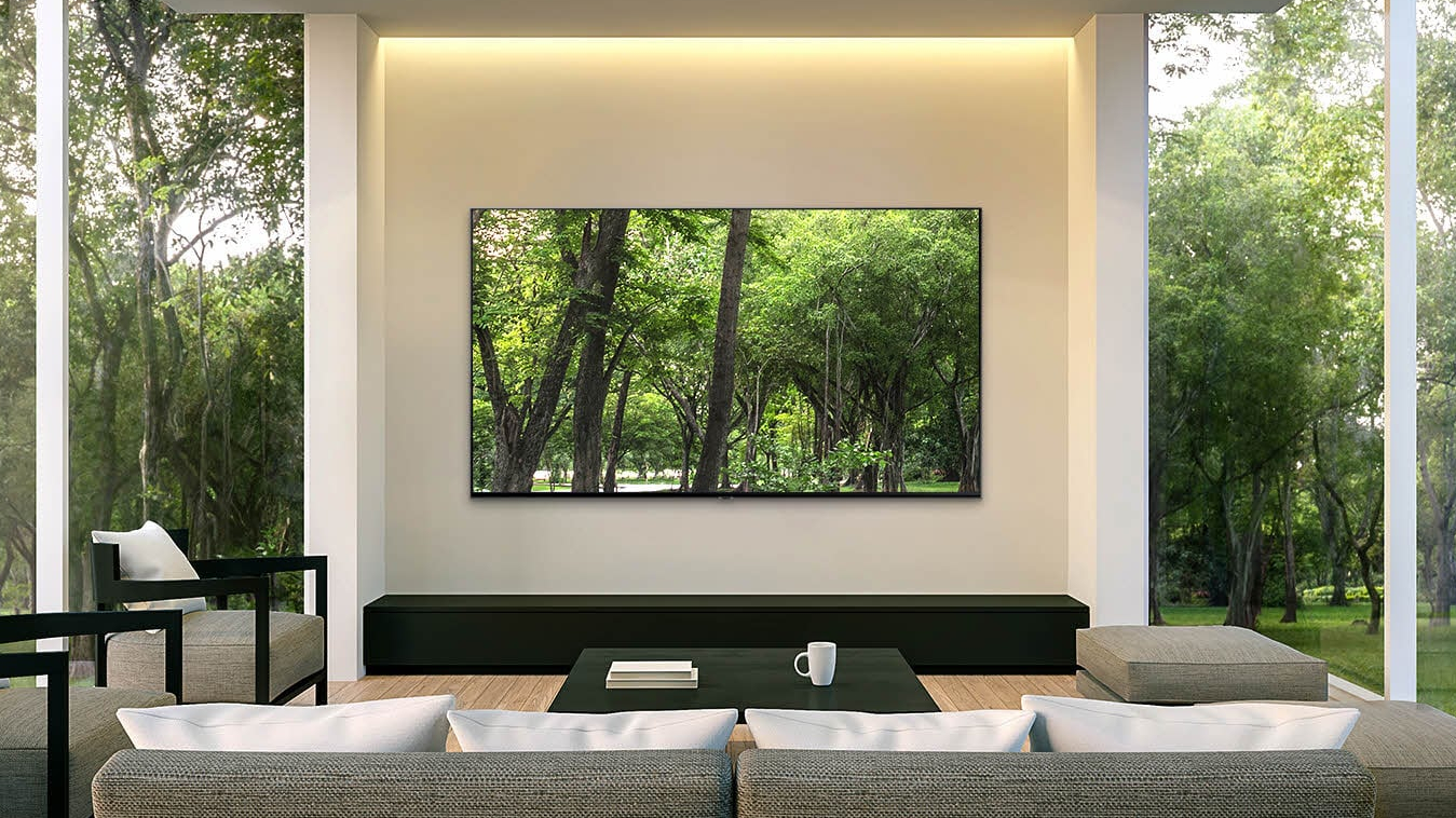 A Samsung Q85 QLED TV wall-mounted in a nice home theater setup