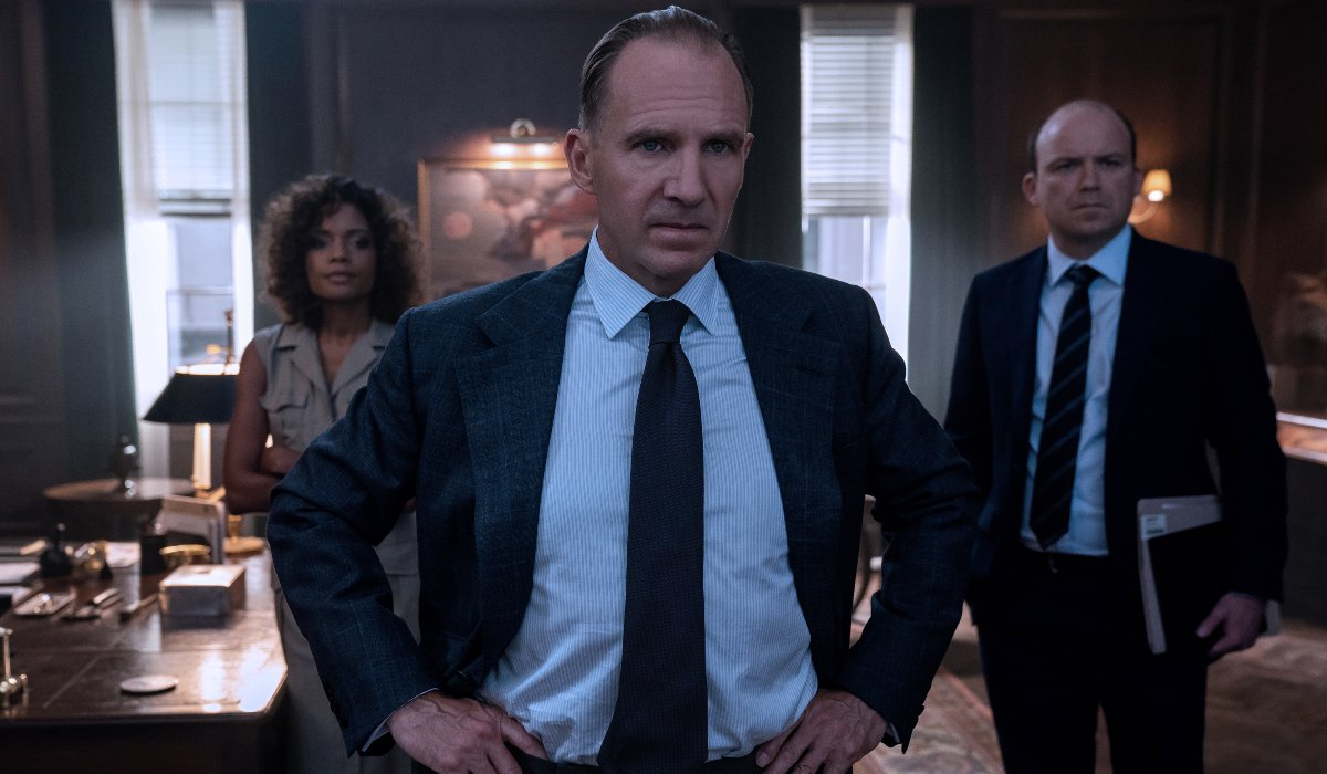 Naomie Harris, Ralph Fiennes, and Rory Kinnear standing around the office in No Time To Die.