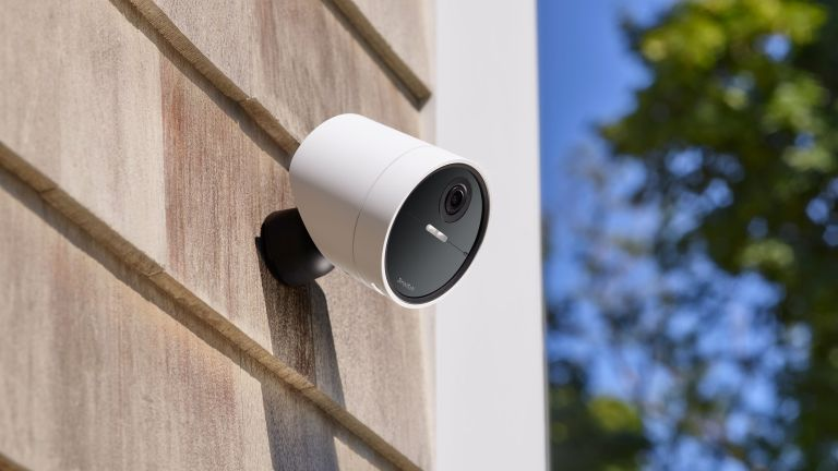 SimpliSafe wireless outdoor security camera on the side of a house in night time with a spotlight shining down