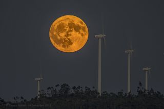 The full Harvest Moon rises over a windmill power plant near Mertola, Portugal, in this photo taken by José Zarcos Palma on Sept. 24, 2018.